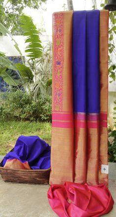 This beautiful kanchivaram silk is in berry blue. The border is in hot pink with thread work in light green, carrot orange and blue along with gold zari work, while the pallu is in hot pink enmeshe…