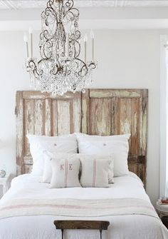 I love the rustic headboard with the ultra elegant chandelier!!! I find so much beauty in the simplicity of this photo.