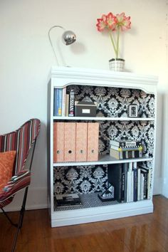 Using demask walpaper to line the back of the bookcase. What a fabulous visual effect.