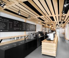 Timber ceiling with suspended spotlights complete the minimalist look of the shop underneath.