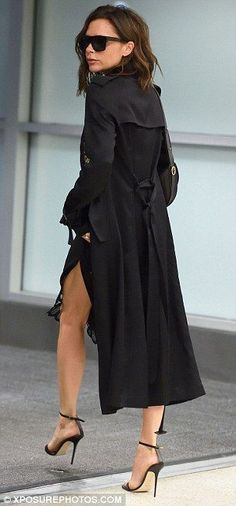 Victoria Beckham wearing a black trench coat & slip dress from her own collection.