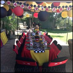 Kids party table styled for Mickey Mouse inspired birthday party. By Distinctive Party Designs.