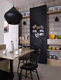 Salle à diner avec tableau noir coulissant. Papier-peint à motifs géométriques et tablettes. Vintage.