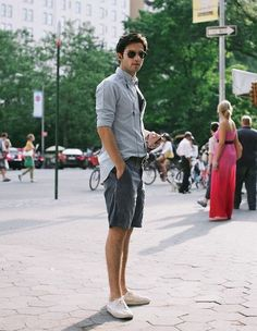 Make a grey long sleeve shirt and charcoal shorts your outfit choice for a trendy and easy going look. A pair of white low top sneakers will seamlessly integrate within a variety of outfits.   Shop this look on Lookastic: https://lookastic.com/men/looks/long-sleeve-shirt-shorts-low-top-sneakers-belt-sunglasses/12257   — Black Sunglasses  — Grey Long Sleeve Shirt  — Black Leather Belt  — Charcoal Shorts  — White Low Top Sneakers