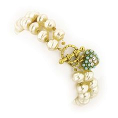 A vintage inspired dual strand, simulated pearl stretch bracelet. Set in antique gold tone, the bracelet features a heart toggle inlaid with turquoise beads. A classic, staple item for any closet.