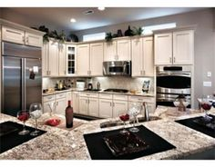 """Layout concept. Has several features I would like:  Open Large bar island Sink in island Dbl oven near stove  We would include: Dishwasher in island 48"""" gas range w built in griddle Different colors w contrasting cupboards from island"""
