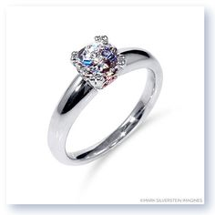 A clean and simple modern ring classically inspired, this 18K white gold ring is rounded tube that tapers from the center stone down.  Pink diamond accents on 18K rose gold add a nice surprise to the glimmer and brilliancy of the ring.     AHAVA>>>>>>LOVE!!!!!!!