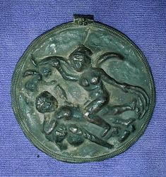 Bactrian repoussé silver  pendant.  This large round silver pendant depicts Selene, the Greek moon goddess, and her lover the shepherd Endymion, along with Eros at left.  1st to 2nd Century AD.  About 12 cm diameter.  Weight is 90.6 g.  From Afghanistan.  It is very similar in design to a somewhat larger plaster tableau recovered from Begram (currently being exhibited with the Afghanistan: Hidden Treasure exhibition).   Picture