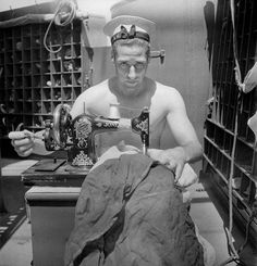 A Royal Navy sailor on board HMS Alcantara uses a portable sewing machine to repair a signal flag during a voyage to Sierra Leone March 1942 ~ Cecil Beaton