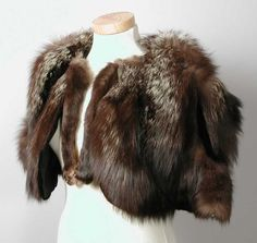 1930-1940 pelerine van langharig bruin met grijs bont, op zwart fluweel genaaid, voering van zwart zijdesatijn, afhangende poten van het dier vormen de sluiting, zilvervos