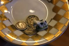 Plum pudding charms, silver threepenny bits, one ready-drilled to wear as a charm and an old porcelain 'fève' from a French Gallette des Rois - Twelfth Night Cake.