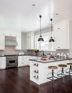 Contemporary kitchen features a beadboard ceiling over a white shaker cabinets adorned with oil rubbed bronze hardware and a gray quartz countertops, Caesarstone Lagos Azul, and a gray mosaic tile backsplash.