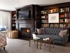 dark shelves filled with books & art, fireplace, white curtains and the couch!!! this is a dream room!!!!!