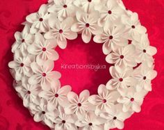 Origami kusudama paper flower wreath!  This beautiful Origami Flower Wreath would be a stand out on your front door!! This could be used as a centerpiece, candle decor or used as party decor. This would also be the perfect gift for that someone special! The possibilities are endless!    This wreath is adorned with 26 flowers made from specialty scrapbook paper that are cut into 3x3 then folded into a petal to be combined to make a beautiful flower. The span of the flower is approx 3. They…