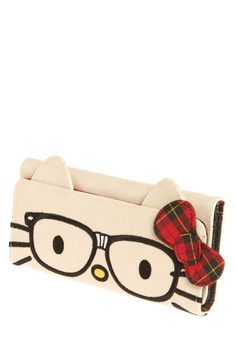 "Nerd Hello Kitty Wallet. I feel apologetic about loving this. ""You also may love Hello Kitty, who matter-of-factly peers out from her eyeglasses on the front flap of this trifold pocketbook. With a collegiate, tartan bow and tape reinforcing the nose bridge on her spectacles, you can be sure that this cat is going to earn you an 'A+' in fashion."""