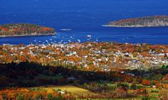 Fall view of Bar Harbor from atop Cadillac Mountain with village in foreground and blue waters in background.
