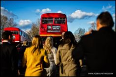 Wedding guests about to board a couple of London buses -