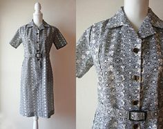 This is a Japanese vintage 1970s shirt dress. It is made of a black and grey polyester fabric with layered white flowers embroidered around small see-through eyelets. The fabric, although beautiful, doesnt have much drape, probably because the dress has never been worn. A few washes might soften it and make it yours. The dress opens with a row of four square buttons in the front. The belt is included. Size: Japanese size 11 (S - S/M) Material: 100% polyester - unlined No brand label, mad...
