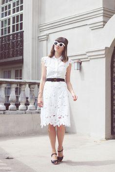 White retro style sunglasses, white floral lace cutouts dress, black belt, and black sandals