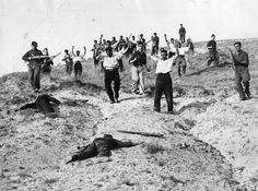 Spain - 1936-39. - GC - Surrendering Republican fighters are marched down the hill, past the bodies of fallen Fascist fighters,