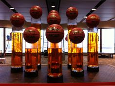 Basketballs sitting on the top of glass with water in the vases. Visit www.fancyfaces.com to get this look.