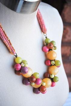 Tutti Fruity Cluster on Silk is created with 18mm calcite rounds and accented with clusters of olive jade, coral, smokey quartz, peridot jasper and antique brass.  The India silk allows the necklas to be adjustable in length. $104