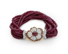 A Multi-strand Ruby and Diamond Bracelet, by Cartier. Composed of nine strands of ruby beads measuring approx. 3.3 mm, the clasp of flower design centered by a cabochon ruby mounted in yellow gold prong claw setting, framed by pavé-set diamond leaves mounted in platinum upon second row of leaves consisting of pavé-set rubies in yellow gold and terminated by pavé-set diamonds. Length 21 cm. French assay marks for gold and platinum.