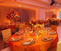 Textured orange linens and high and low arrangements of persimmons, roses and ranunculi topped tables in the reception area.