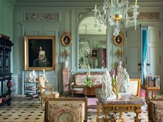 Resting beneath a mirror in the central salon of a French château is a gilt-wood canapé that belonged to the 18th-century hostess Madame Geoffrin; the antique Sèvres statuettes depict literary figures