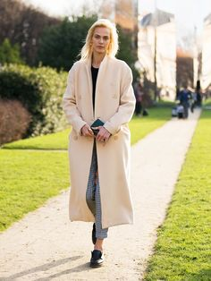 Aymeline Valade in a pastel peach coat, checked trousers and chunky black flat shoes.