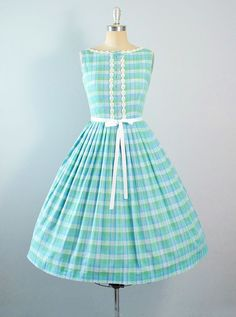 ♦ Vintage 1950s Sundress. ♦ Constructed in a Green, Blue & a Hint of Silver, Plaid Stripes Cotton Fabric. ♦ Boat Scoop Neckline with a Tiny Bow &
