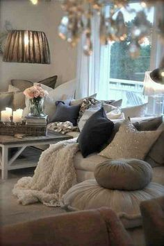 The keys to a cozy living room area: natural wood accent (TV stand, can distress/ikea hack), lots of pillows (big comfy soft ones, again ikea), candles, mood lighting, flowers
