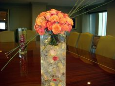 Unique corporate floral arrangement.  Orange roses, tall vase, rose cluster and horse tail.