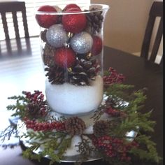 Table centerpiece, silver plate charger, epson salt for snow, pine cones, ornaments, and cranberries from Hobby Lobby. Inexpensive and pretty.