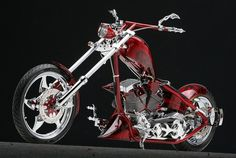 dark red custom chopper with chrome forks and chrome twin engine and candy apple paint.