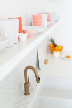 An extended floating shelf elevates kitchen storage. Brushed brass drawer pulls and faucet pop against a white penny tile backsplash.
