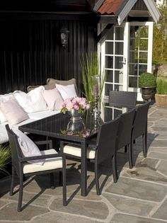 De svarte hagemøblene står i fin stil til husets fasade. Et lass av puter gjør de både lekre å se på og komfortable å sitte i.