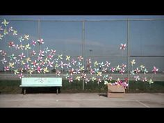 Pinwheels become a kinetic sculptural piece when staged on a chain-link fence by Kate Spade