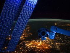 With hardware from the Earth-orbiting International Space Station appearing in the near foreground, a night time European panorama reveals city lights from Belgium and the Netherlands at bottom center, the British Isles partially obscured by solar array panels at left, the North Sea at left center, and Scandinavia at right center beneath the end effector of the Space Station Remote Manipulator System or Canadarm2. ISS030-E-048067 (22 Jan. 2012)