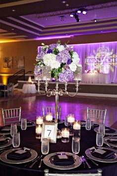 Purple and white floral in a bling candelabra make a great wedding reception centerpiece! Vangie's Events of Distinction, Blossoms Arrangements of Distinction, Orlando, Florida.