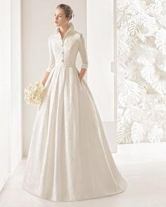 Vestido de novia clásico de costura de brocado de seda, con cuello camisero abierto con botones, manga tres cuartos y falda de pliegues, en color natural.