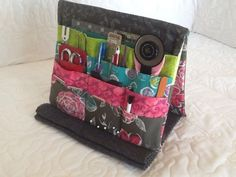 """The tool holder is large enough for a 4″ x 8″ cutting mat and ruler, 45mm rotary cutter, pins, needles, seam ripper, pencil(s), and more!  This is a super easy project that anyone with sewing skills can complete. Plus, you can easily customize the pocket sizes to fit your tools.  The finished size is 9.5″ W x 7.5″ L x 1.5″ D when closed and 9.5″ W x 7.5″ L x 7″ D when standing open.  Click here to purchase the """"Tooly Tool Holder Easel"""".         Things You May Need to Finish Your Project…"""