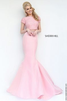 New for 2015...Sweet and enchanting well describes the two-piece ensemble of Sherri Hill 32248 prom dress, decked with a pearl-beaded crop top that leaves a bare midriff. The jewel neckline is framed by the short sleeves, both bordering the circular cutout over the rear. Micro beads gild the band cinching the natural waist, grandly presenting the princess seamed mermaid skirt that glides over the floor with a brush train. Available in Ivory and Blush as shown.