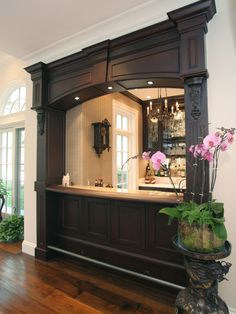 A gorgeous recessed pass-through bar between the kitchen and living space! The architectural molding and color choice are both superb. This is absolutely beautiful and a great idea for opening up the kitchen! | Caption by Jenn Brown