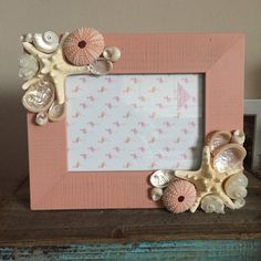 This beautiful beach inspired pink picture frame features natural pink sea urchins. I also used white knobby starfish, abalone shells and pearlized turbo shells. This frame has a rectangle shape that is 10 by 9 inches. It fits a 5x7 size picture. I accept custom orders- if there is a design you have in mind, I would love to work with you, just message me