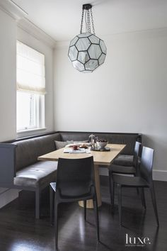 A simple modern dining nook with banquette and pendant light.