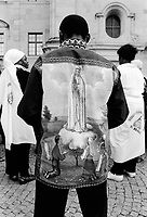 """Switzerland. Canton Schwyz. Einsiedeln Abbey. African pilgrimage. Various religious african communities coming from allover Switzerland and southern Germany celebrate their faith and belief in Jesus Christ. A black man wears a shirt with drawing of """"Our Lady of Fátima """" a title for the Virgin Mary due to her reputed apparitions to three shepherd children at Fátima, Portugal in 1917. The title of Our Lady of the Rosary is also sometimes used to refer to the same apparition. According to…"""