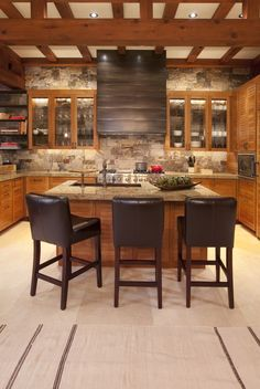 Brown leather barstools are a fun accent to this rustic kitchen by Studio Frank.