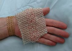 Two sizes of knotted chain mail knit together. Each of the rings is shaped into a knot before linking.