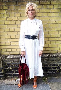 A white long sleeve maxi dress is worn with a black belt, fringe red bag, and orange sandals.